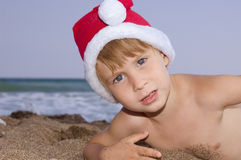 Christmas boy play on the beach Royalty Free Stock Photography