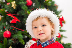 Christmas boy. Portrait of happy little boy in Santa hat near Christmas tree Stock Photography
