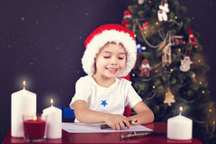 Christmas boy writing letter to Santa. Christmas boy in the red hat writing letter to Santa on red table with candles and christmas thee Royalty Free Stock Image