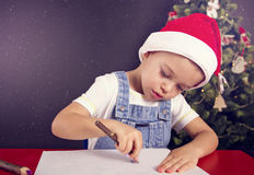 Christmas boy writing letter to Santa. Christmas boy in the red hat writing letter to Santa on red table with candles and christmas thee Stock Photography