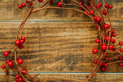 Christmas branch with red berries. On a rustic wooden background Stock Image