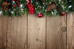 Christmas branch top border on rustic old wood. Christmas branch top border with berries and pine cones on a rustic old wood background Royalty Free Stock Photos
