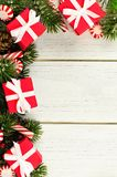 Christmas branches, gifts and candy canes border on white wood Royalty Free Stock Image