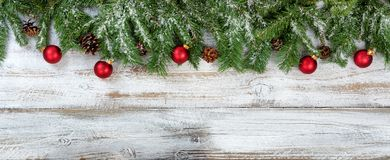Christmas branches and ornaments on rustic white wooden backgrou. Christmas evergreen branches and red ornaments background stock images
