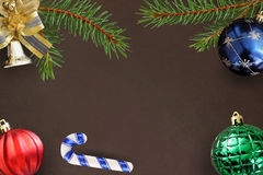 Christmas branches of spruce, stick, blue, green ribbed, red balloon and decorative bell on dark background Stock Photos