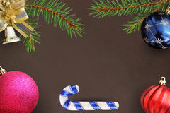 Christmas branches of spruce, stick, blue, pink and red balloon, decorative bell on dark background Stock Photos