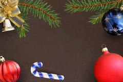 Christmas branches of spruce, stick, blue and red wavy balloon and decorative bell on dark background Royalty Free Stock Photography