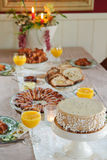 Christmas Breakfast. Beautiful table set for a festive christmas breakfast or brunch, with star rolls, christmas bread, white chocolate cake and candles Stock Photo