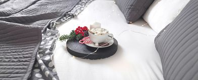 Christmas Breakfast in bed with a Cup of Coffee gift boxes, garlands and Christmas composition. stock photo