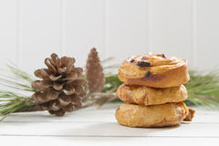 Christmas breakfast. A heap of danish puff pastry swirls and some pinecones on a white wooden table Stock Photography