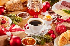 Christmas breakfast table with food and ornaments. Christmas Intercontinental breakfast table with an assortment of tasty fresh food, coffee, gifts and colorful stock photo