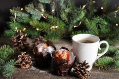 Christmas Breakfast of two cupcakes and a Cup of hot coffee sprinkled with powdered sugar, on the background of fir branches with stock photos