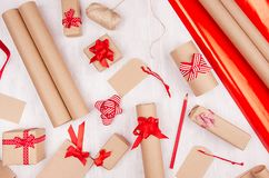 Christmas bright background - festive gift boxes with red bows and ribbons, rolls wrapping paper, blank labels on soft white wood. stock images