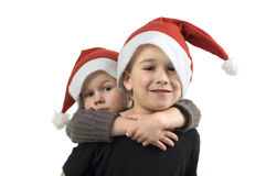 Christmas Brothers. Two brothers with Christmas hats. On white background Royalty Free Stock Images