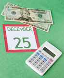 Christmas on a Budget. Calendar page with currency and a calcular for a tight budget this Holiday season Royalty Free Stock Photography