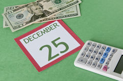 Christmas on a Budget. Calendar page with currency and a calcular for a tight budget this Holiday season.  Be careful not to overspend Stock Images