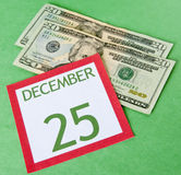 Christmas on a Budget. Calendar page with currency for a tight budget this Holiday season Royalty Free Stock Photo