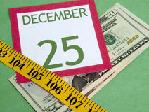 Christmas on a Budget. Christmas calendar page squeezed by a measuring tape representing a tight holiday budget Royalty Free Stock Image