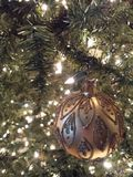 Christmas bulb on a lighted tree. Gold Christmas bulb hanging on a lighted Christmas tree Royalty Free Stock Images