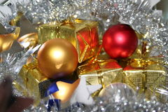 Christmas bulbs. And gold presents surrounded by silver garland royalty free stock image