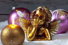 Christmas bulbs burning candle golden putto on pile of snow Royalty Free Stock Photos