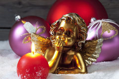 Christmas bulbs burning candle golden putto on pile of snow Stock Image