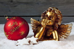 Christmas bulbs cinnamon stars golden putto on pile of snow Stock Image