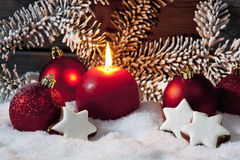 Christmas bulbs cinnnamon stars pine twig candle on pile of snow against wooden wall Royalty Free Stock Photos