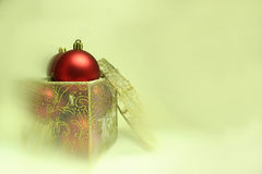 Christmas Bulbs in a Present Box. Red christmas bulbs in a gift box on a blurred background Royalty Free Stock Image