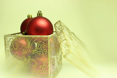 Christmas Bulbs in a Present Box. Red christmas bulbs in a gift box on a blurred background Stock Image
