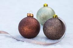 Christmas bulbs on snow Stock Photos
