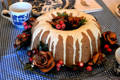 Christmas Bundt Cake. A Christmas Cranberry frosted bundt cake sitting on a table with blue gingham tablecloth and blue and white tea cups and plates Royalty Free Stock Photography