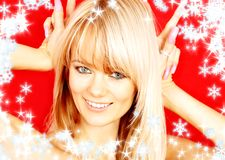 Christmas bunny over red. Christmas portrait of lovely blond with bunny ears gesture over red Stock Image