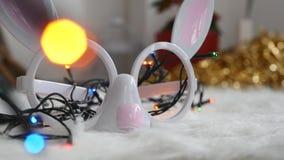 Christmas bunnys glasses. Closeup of bunny glasses and colorful lights, christmas theme stock video