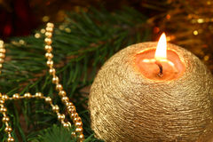 Christmas burning candle. Golden burning candle and Christmas tree branch with globule chain Royalty Free Stock Photography