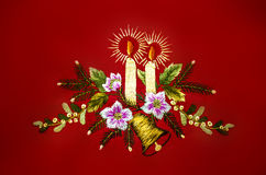 Christmas with burning candles,bell and flowers,embroidered  on red background Stock Photos