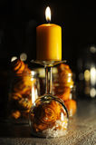Christmas burning orange candle. Tangerine peel roses and artificial snow inside a inverted wine glass Royalty Free Stock Photography