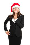 Christmas business woman thinking looking to side. Christmas business woman thinking looking to the side wearing santa hat and business suit. Multi-racial santa Stock Photo