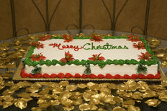 Christmas cake. Large christmas cake on a bed of gold foliage Stock Photography