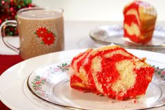 Christmas Cake. Festive red and yellow swirled Christmas cake on holiday dinnerware Stock Image