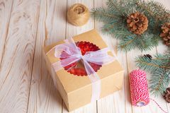 Christmas cake and cookies in delivery packing box with berries. Christmas cake in box with berries in delivery packing box on white wooden background Royalty Free Stock Photos