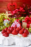 Christmas cake covered with cream and topped with strawberries Royalty Free Stock Photos