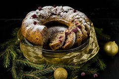 Christmas cake with cranberries and walnuts. On a black background with the decoration of fir branches and Christmas Ornaments Royalty Free Stock Photography