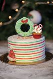 Christmas cake decorated with Christmas cupcakes and colorful sweets royalty free stock images