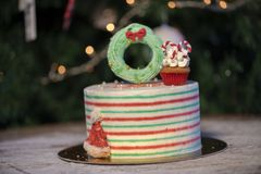 Christmas cake decorated with Christmas cupcakes and colorful sweets stock image