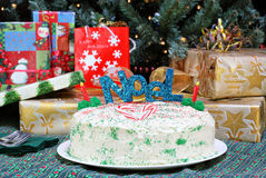 Christmas cake in front of tree and gifts. Decorated Christmas cake in front of a lit Christmas tree and gifts, evening setting Royalty Free Stock Photo