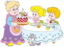 Christmas cake. Granny and her grandchildren at the holiday table with a Christmas cake Royalty Free Stock Photos