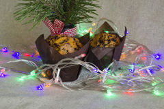 Christmas cake with lights on a light background. Christmas cake in paper packing, Christmas lights and pine bouquet on a linen background Stock Photography