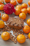 Christmas cake with mandarins. Traditional Chrismtas cake with almonds and raisins on the table surrounded with mandarins stock photo