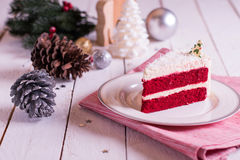 Christmas cake on plate on red fabric on wood background and dec Royalty Free Stock Photo